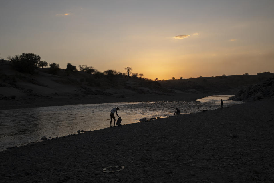 People stand on the banks of the Tekeze River, on the Sudan-Ethiopia border after Ethiopian forces blocked individuals from crossing into Sudan, near Hamdayet, eastern Sudan, on March 16, 2021. Ethiopia is at left, and Sudan is at right. (AP Photo/Nariman El-Mofty)