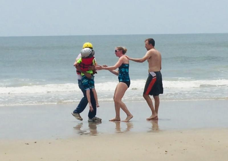 The boy is returned to his relieved mum and dad on the beach at Oak Island.