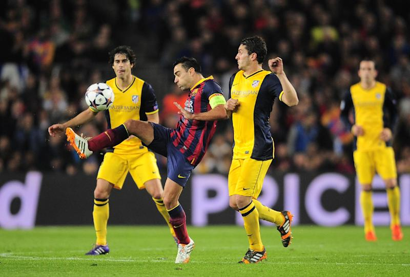 Barcelona's Xavi Hernandez, centre controls the ball in front of Atletico's Koke, right, during a first leg quarterfinal Champions League soccer match between Barcelona and Atletico Madrid at the Camp Nou stadium in Barcelona, Spain, Tuesday April 1, 2014