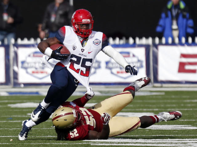 Arizona running back Ka'Deem Carey (25) is shirt tackled by Boston College linebacker Steven Daniels (52) during the second half of the AdvoCare V100 Bowl NCAA college football game, Tuesday, Dec. 31, 2013, at Independence Stadium in Shreveport, La. Arizona won 42-19 (AP Photo/Rogelio V. Solis)
