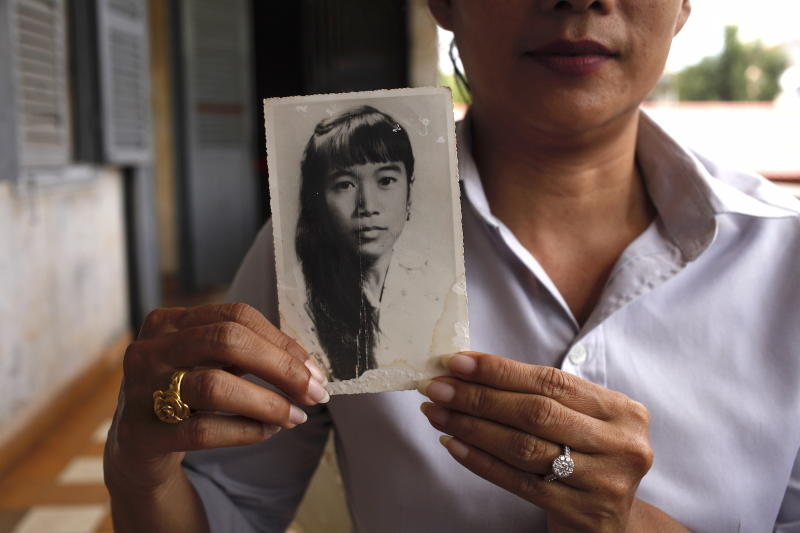 Chheng Samin was born under a pagoda shortly after the fall of Phnom Penh. She holds a picture of her mother, Chheng Samit, who survived the Khmer Rouge but died young. She now works at Tuol Sleng. | Photographer: Andy Kopsa