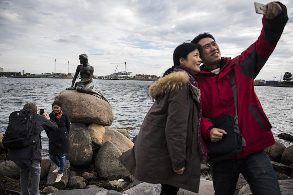 """Tourists photograph themselves with the bronze statue """"The Little Mermaid"""" at the harbour in Copenhagen on October 9, 2015. Based on the fairy tale of the same name by Danish author Hans Christian Andersen, the statue has become an icon and a major tourist attraction in the Danish capital since 1913. In recent decades it has become a popular target for defacement by vandals and political activists.  AFP PHOTO / ODD ANDERSEN        (Photo credit should read ODD ANDERSEN/AFP/Getty Images)"""