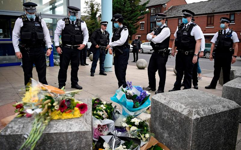 Police officers wearing protective face masks, pay their respects outside the Croydon Custody Centre - DANIEL LEAL-OLIVAS/AFP via Getty Images