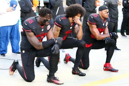 San Francisco 49ers outside linebacker Eli Harold (58), quarterback Colin Kaepernick (7) and free safety Eric Reid (35) kneel during the national anthem before the game against the Arizona Cardinals at Levi's Stadium. Mandatory Credit: Kelley L Cox-USA TODAY Sports
