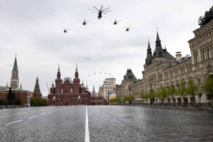 Russian military helicopters fly over over almost empty Red Square to mark the 75th anniversary of the Nazi defeat in World War II in Moscow, Russia, Saturday, May 9, 2020. A massive Victory Day parade on Red Square was cancelled due to the coronavirus outbreak, but Russia marked the holiday with the flyby. (AP Photo/Alexander Zemlianichenko)