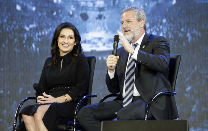 At a Liberty University convocation in November 2018, Jerry Falwell Jr. gestures while speaking, as his wife, Becki, listens.