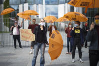 Activists of the Generation-Foundation hold symbolic rescue umbrellas in their hands during a protest in front of the chancellery in Berlin, Germany, Thursday, May 28, 2020. The Generation-Foundation is focusing on climate change and social justice and demand a change of the system for the further generations. The inscriptions on the umbrellas read: 'Generation Rescue Umbrella' - 'Climate Justice Democracy'. (AP Photo/Markus Schreiber)