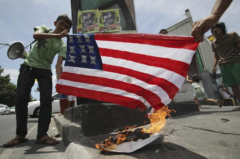 Filipino activists burn a mock U.S. flag as they hold a short protest in Manila, Philippines on Sunday April 27, 2014. The group is opposing the visit of U.S. President Barack Obama and a looming pact that will increase the American military presence in the Philippines. (AP Photo/Aaron Favila)
