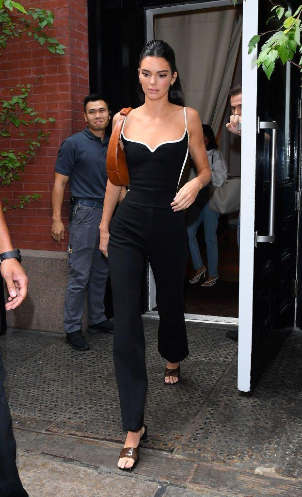 <p>Jenner accessorised her black and white outfit with mules and a brown, structured handbag.</p>