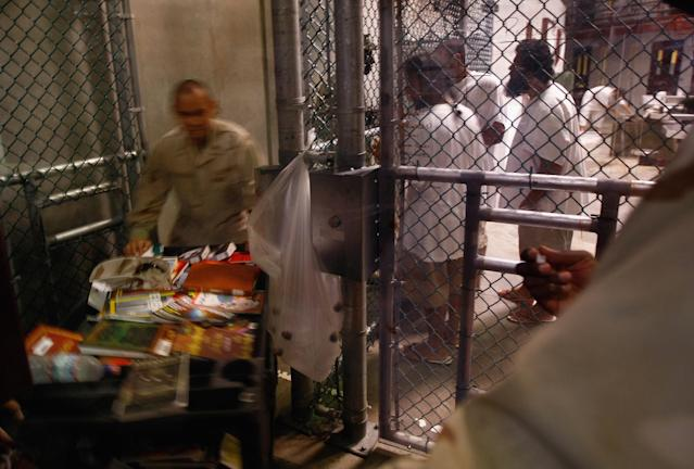 """GUANTANAMO BAY, CUBA - OCTOBER 27: (EDITORS NOTE: Image has been reviewed by U.S. Military prior to transmission.) A military librarian brings out books read by detainees inside the U.S. military prison for """"enemy combatants"""" on October 27, 2009 in Guantanamo Bay, Cuba. Although U.S. President Barack Obama pledged in his first executive order last January to close the infamous prison within a year's time, the government has been struggling to try the accused terrorists and to transfer them out ahead of the deadline. Military officials at the prison point to improved living standards and state of the art medical treatment available to detainees, but the facility's international reputation remains tied to the """"enhanced interrogation techniques"""" such as waterboarding employed under the Bush administration. (Photo by John Moore/Getty Images)"""