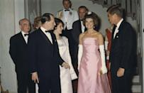 <p>Jackie stuns in a pale pink strapless gown as she and the President greet guests for an official dinner at the White House. </p>