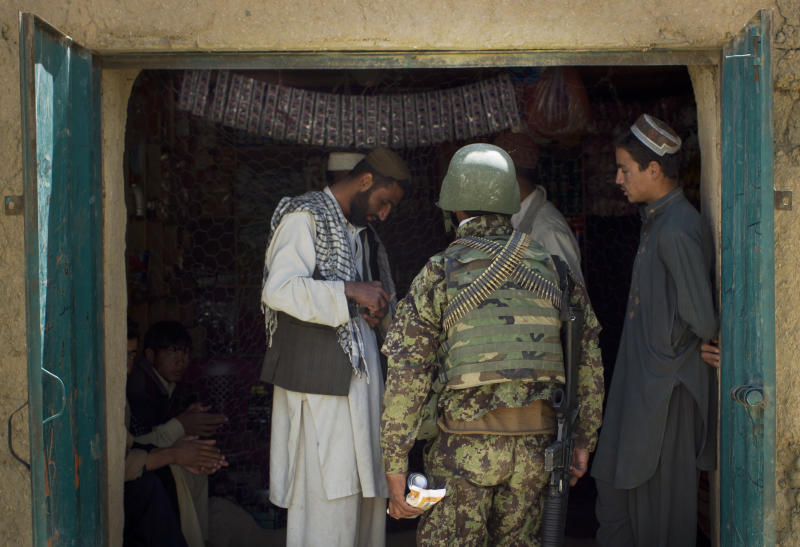 An Afghan National Army soldier buys soft drinks in a shop while on patrol in Logar province, east Afghanistan, Thursday, May 17, 2012. NATO sits down May 20, 2012 in Chicago to prepare for the eventual withdrawal of international forces and the hand over of Afghanistan's security to the Afghan National Army. (AP Photo/Anja Niedringhaus)