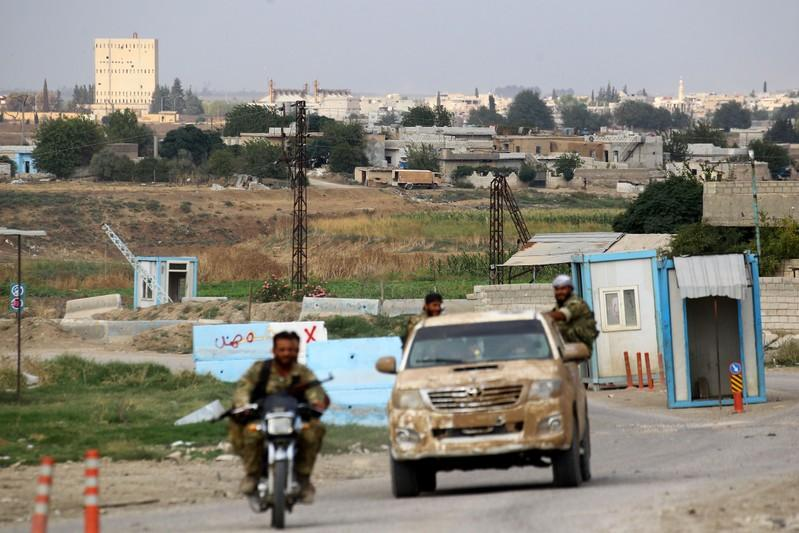 Buildings and houses are seen as Turkey-backed Syrian rebel fighters patrol near Ras al Ain Town