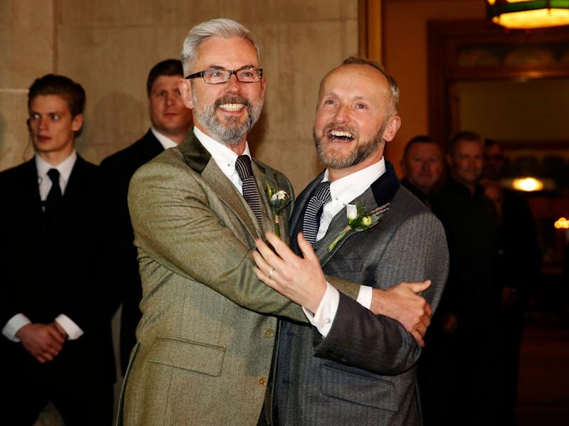 Gay couple Andrew Wale (L) and Neil Allard reacts to crowds, friends, family and the press after marrying in the first same-sex wedding in Brighton, at the Royal Pavilion in southern England March 29, 2014. Saturday will be the first day gay couples will be allowed to tie the knot in England and Wales after the government legalised same-sex marriage last July. Wale and Allard are the first out of five same-sex couples tying the knot in Brighton on Saturday. REUTERS/Luke MacGregor (BRITAIN - Tags: SOCIETY)