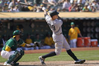 New York Yankees' Aaron Judge (99) hits a two-run home run in front of Oakland Athletics catcher Yan Gomes during the ninth inning of a baseball game in Oakland, Calif., Saturday, Aug. 28, 2021. (AP Photo/Jeff Chiu)