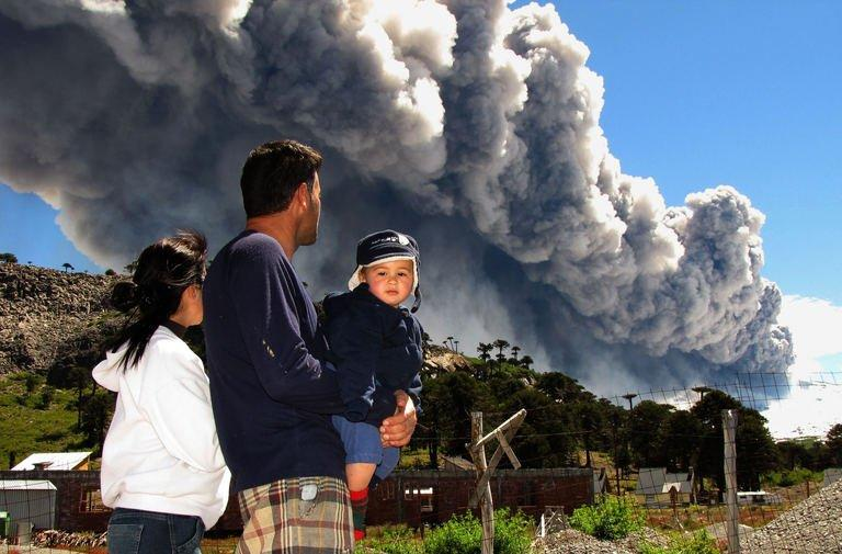 A family watches the Copahue volcano spewing ash from Caviahue, Argentina on December 22, 2012