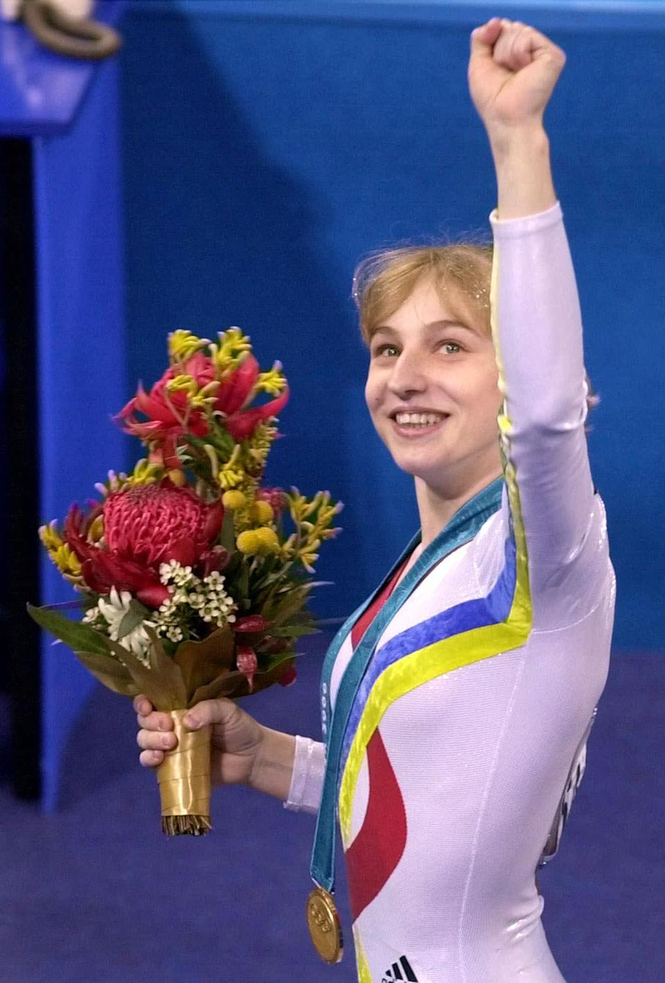 <p>Gold medalist Simona Amânar of Romania waves to the crowd after the awards ceremony for the women's gymnastic all-around at the 2000 Summer Olympic Games in Sydney. (AP Photo/Ed Reinke) </p>