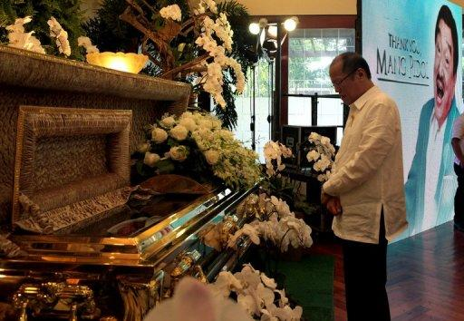 Philippine President Benigno Aquino offers prayers next to the casket of the late comedian Rodolfo Vera Quizon