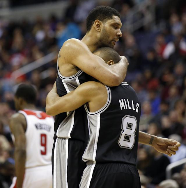 San Antonio Spurs forward Tim Duncan, top, embraces guard Patty Mills (8), from Australia, during a timeout in the first overtime of an NBA basketball game against the Washington Wizards, Wednesday, Feb. 5, 2014, in Washington. Duncan had 31 points and Mills had 23 in their 125-118 double overtime win. (AP Photo/Alex Brandon)