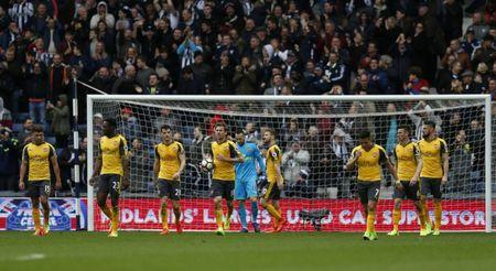 Arsenal players look dejected after West Bromwich Albion's Craig Dawson scored their third goal