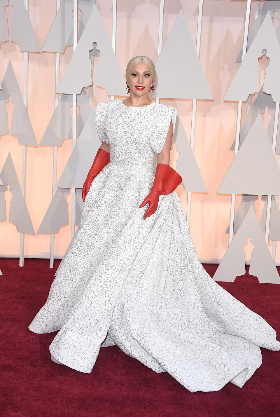 """<p>Years before she took home a statue of her own, Gaga made her Oscar debut in a billowing white gown with bizarre red leather gloves. The look spawned countless memes, but Gaga redeemed herself later that night with a show-stopping performance of """"The Sound of Music.""""</p>"""