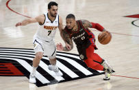 Portland Trail Blazers guard Damian Lillard, right, drives to the basket on Denver Nuggets guard Facundo Campazzo, left, during the first half of an NBA basketball game in Portland, Ore., Sunday, May 16, 2021. (AP Photo/Steve Dykes)