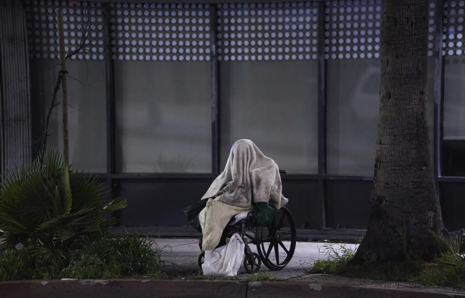 FILE - In this April 6, 2020, file photo, a homeless person sits in a wheelchair during rainy weather on Sunset Boulevard in the Echo Park neighborhood of Los Angeles. When census takers tried to count the nation's homeless population, they ran into many problems that could threaten the accuracy of the effort. That's what a half dozen census takers around the U.S. tell The Associated Press. (AP Photo/Damian Dovarganes, File)