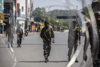 Indian paramilitary soldiers patrol a deserted market area in Srinagar, Indian controlled Kashmir, Thursday, Sept. 2, 2021. Indian authorities cracked down on public movement and imposed a near-total communications blackout Thursday in disputed Kashmir after the death of Syed Ali Geelani, a top separatist leader who became the emblem of the region's defiance against New Delhi. Geelani, who died late Wednesday at age 91, was buried in a quiet funeral organized by authorities under harsh restrictions, his son Naseem Geelani told The Associated Press. He said the family had planned the burial at the main martyrs' graveyard in Srinagar, the region's main city, as per his will but were disallowed by police. (AP Photo/ Mukhtar Khan)