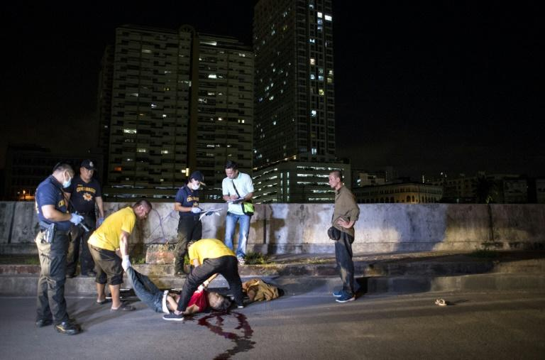 Coroners move the dead body of an alleged drug dealer killed during a police anti-drug operation in Manila on August 18, 2017