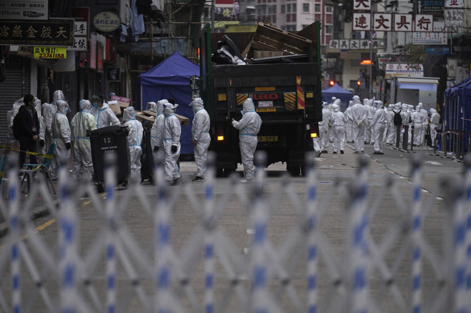 Government workers wearing personal protective equipment gather at the closed area in Jordan district, in Hong Kong, Sunday, Jan. 24, 2021. Thousands of Hong Kong residents were locked down Saturday in an unprecedented move to contain a worsening outbreak in the city, authorities said. (AP Photo/Vincent Yu)