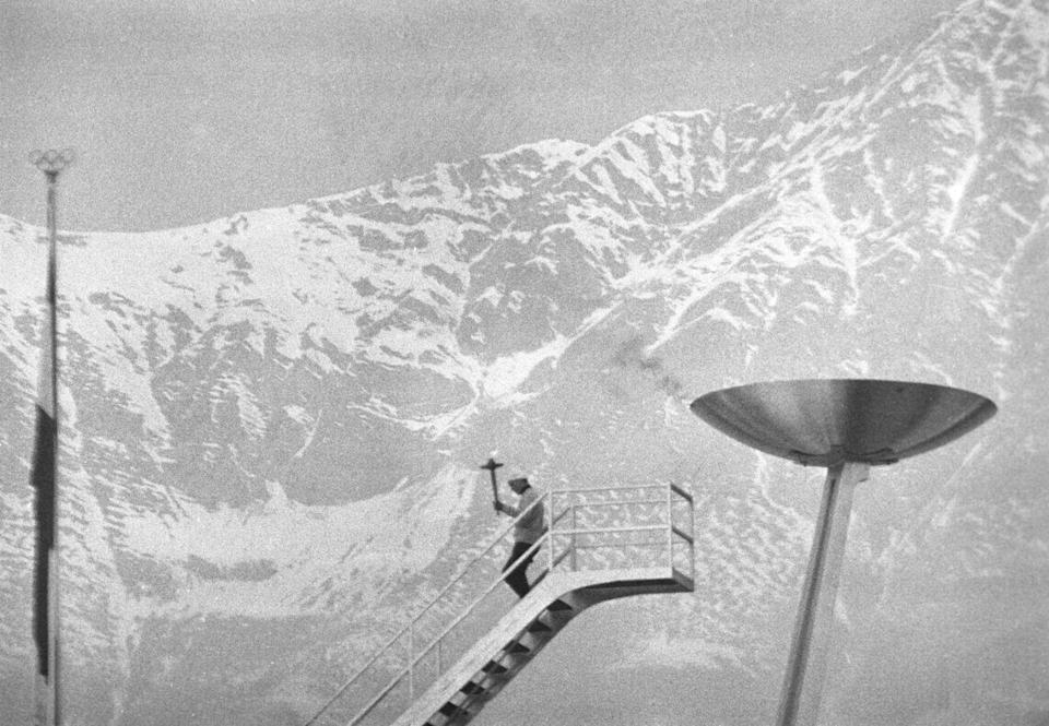 <p>After lighting the Olympic flame during the 1964 Winter Olympic Games in Austria, the torch bearer makes his way down a tall staircase against a stunning mountain landscape. </p>