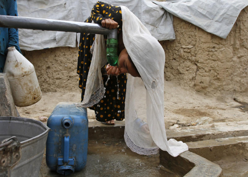 An Afghan girl drinks water near her family's temporary housing on the outskirts of Kabul, Afghanistan, Tuesday, July 30, 2013. (AP Photo/Ahmad Jamshid)