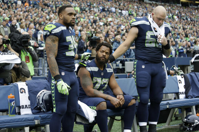 Seattle Seahawks defensive end Michael Bennett, center, is joined by teammates Thomas Rawls, left, and Justin Britt, as he sits during the singing of the national anthem. (AP)
