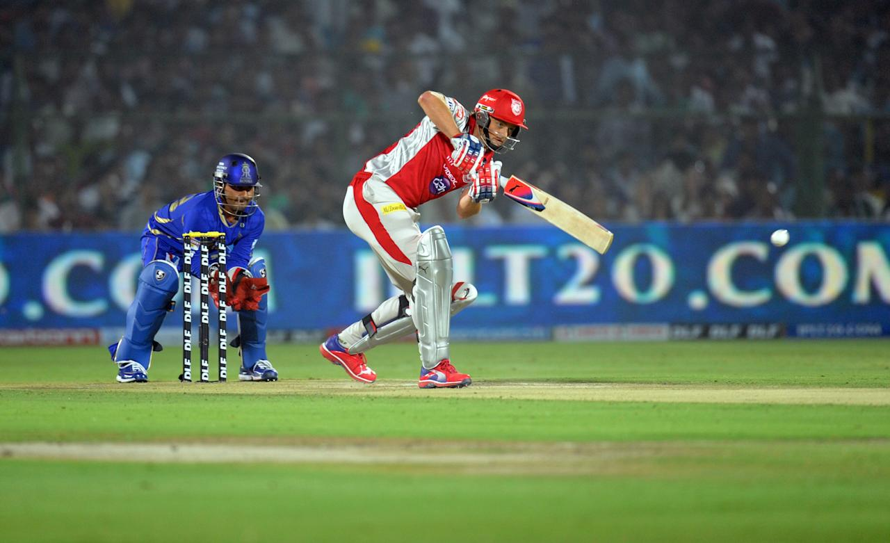 Rajasthan Royals wicketkeeper Shreevats Goswami  looks on (L) as Kings XI Punjab captain Adam Gilchrist plays a shot during the IPL Twenty20 cricket match between Rajasthan Royals and King XI Punjab at the Sawai Mansingh Stadium in Jaipur on April 6, 2012.  AFP PHOTO / RAVEENDRAN RESTRICTED TO EDITORIAL USE. MOBILE USE WITHIN NEWS PACKAGE AFP PHOTO/RAVEENDRAN (Photo credit should read RAVEENDRAN/AFP/Getty Images)