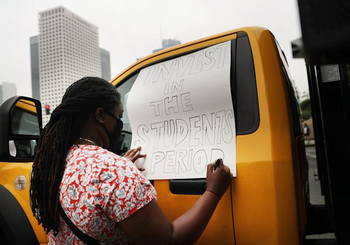 A demonstrator makes a sign reading 'Invest In The Students Period' as Black Lives Matter-Los Angeles supporters protest.