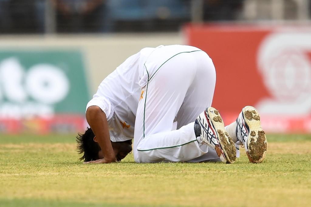 Pakistan's bowler Mohammad Amir touches his forehead on the field in celebration after bowling out West Indies' batsman Alzarri Joseph on day two of their first Test match at the Sabina Park in Kingston, Jamaica, on April 22, 2017 (AFP Photo/Jewel SAMAD)