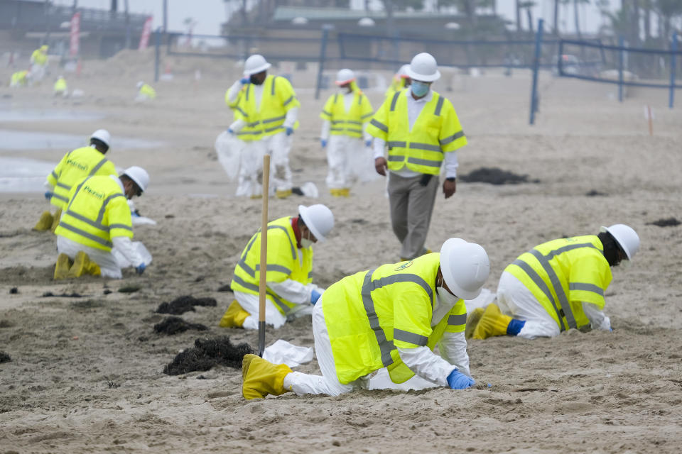 FILE - In this Thursday, Oct. 7, 2021, file photo, workers in protective suits clean the contaminated beach in Corona Del Mar in Newport Beach, Calif. The amount of crude oil spilled in an offshore pipeline leak in Southern California is believed to be close to about 25,000 gallons, a Coast Guard official said Thursday Oct. 14, 2021. (AP Photo/Ringo H.W. Chiu, File)