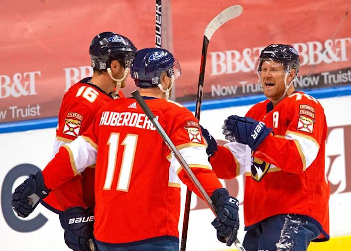 Florida Panthers left wing Jonathan Huberdeau (11) is congratulated by teammates Aleksander Barkov (16) Patric Hornqvist (70) after scoring against the Chicago Blackhawks during the third period of the Florida Panthers NHL home opener game at the BB&T Center on Sunday, January 17, 2021 in Sunrise, Fl.