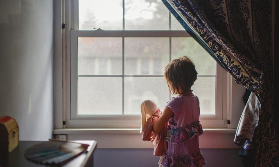 A small child stands by bedroom window tenderly holding stuffed bunny