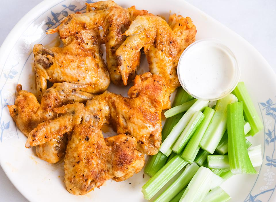 finished chicken wings with blue cheese dip and celery on a plate