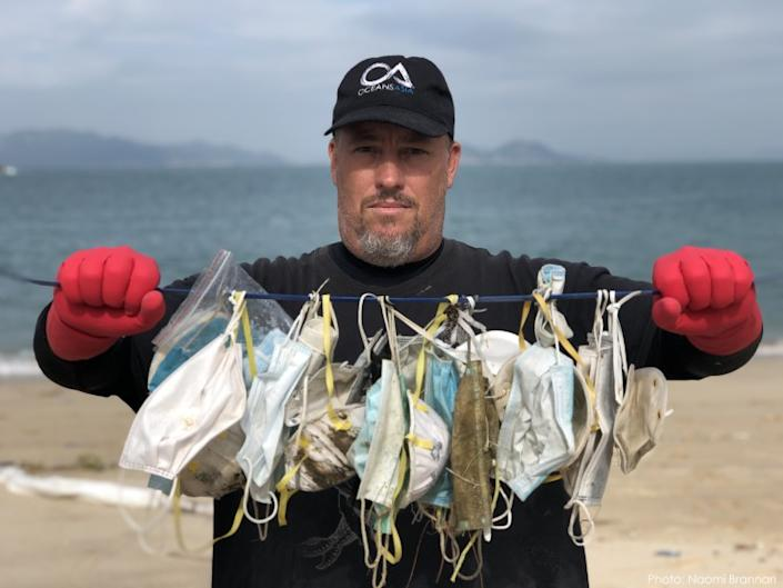 Environmental activist Gary Stokes displays dozens of discarded masks he collected from a Hong Kong beach in February.