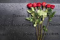 Red roses rest against the names of the fallen on the south pool at the National September 11 Memorial & Museum, Thursday, Sept. 9, 2021, in New York. (AP Photo/John Minchillo)