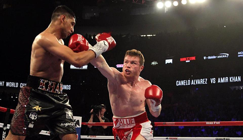 "Saul ""Canelo"" Alvarez (R) connects with a right against Amir Khan. (AFP)"