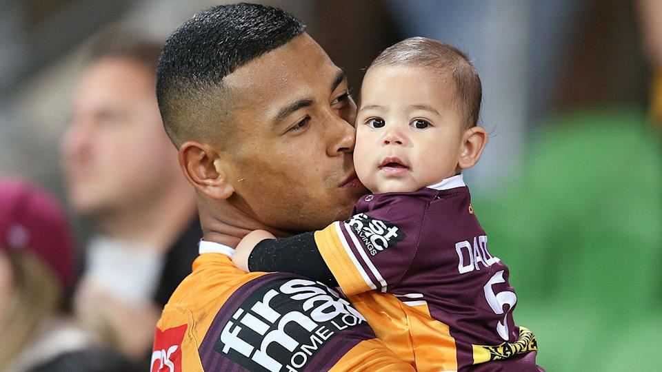 Jamayne Isaako is seen here holding his child after a Brisbane Broncos match.