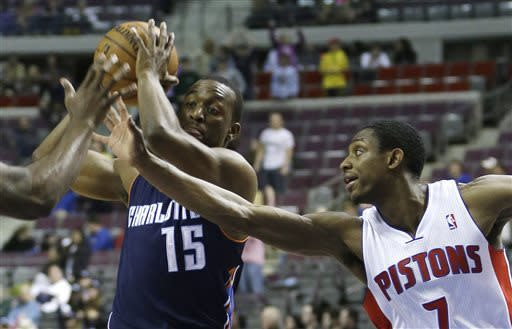 Detroit Pistons guard Rodney Stuckey (out of frame, left) and guard Brandon Knight (7) reach in on Charlotte Bobcats guard Kemba Walker (15) during the first half of an NBA basketball game at the Palace in Auburn Hills, Mich., Friday, April 12, 2013. (AP Photo/Carlos Osorio)