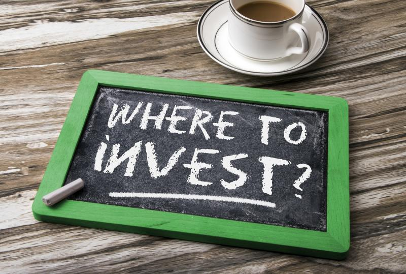 Chalkboard on a table with where to invest written on it.