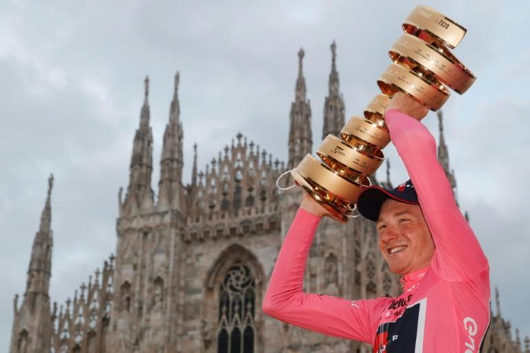 "Tao Geoghegan Hart wearing the leader's pink jersey and holds the ""Never ending trophy"" (Trofeo Senza Fine) in front of Duomo cathedral in Milan"