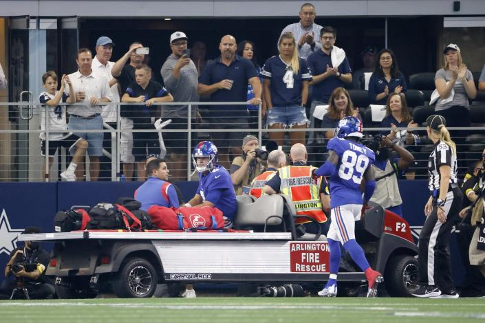 Fans look on as New York Giants wide receiver Kadarius Toney (89) jogs over to talk with quarterback Daniel Jones who is carted off the field after suffering an unknown injury in the first half of an NFL football game against the Dallas Cowboys in Arlington, Texas, Sunday, Oct. 10, 2021. (AP Photo/Ron Jenkins)
