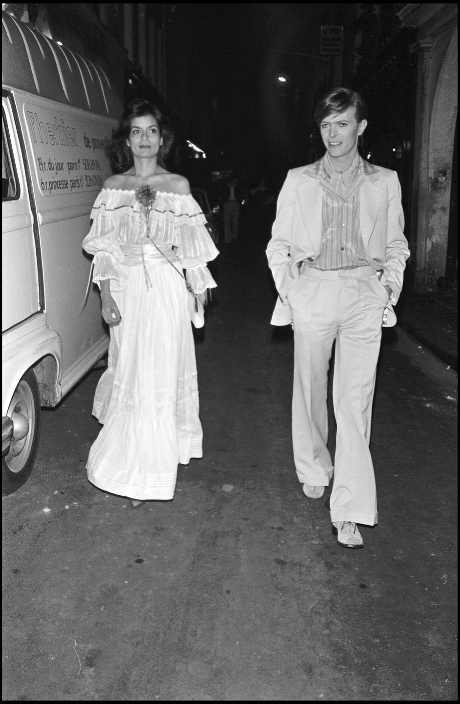 <p>Music legend David Bowie leaves a party in Paris with Bianca Jagger. She would go on to divorce Bowie's close friend, Mick Jagger, just one year later.</p>