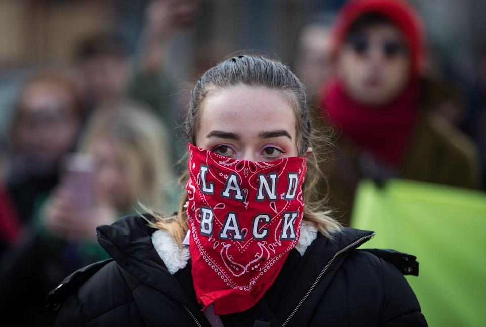 A woman wears a bandana over her face reading 'Land Back'